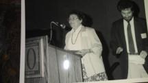 Joan Iversen at podium, Mark Delligatti to the right