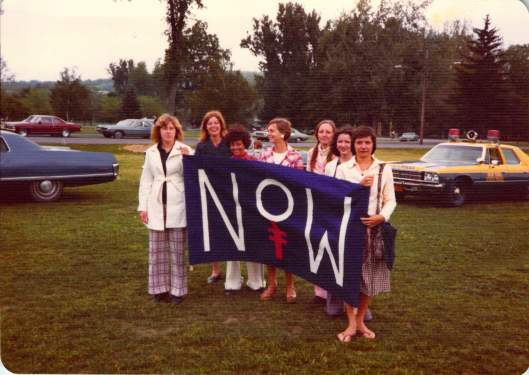 Women holding NOW banner